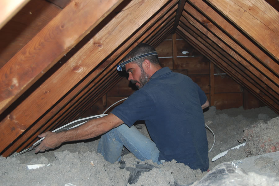 residential electrician working in the attic